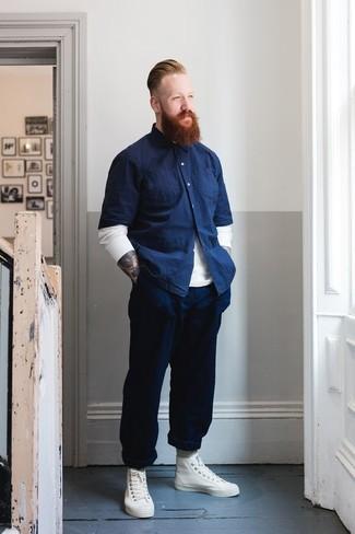 Comment porter: pull à col rond blanc, chemise à manches courtes en chambray bleu marine, pantalon chino bleu marine, baskets montantes en cuir blanches