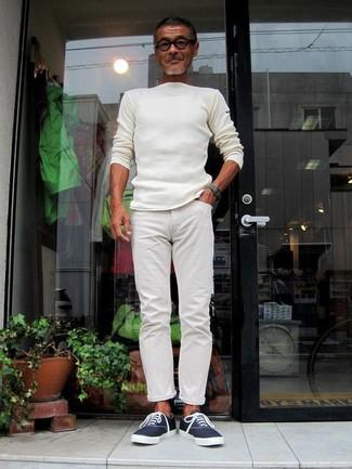 Comment porter: pull à col rond blanc, pantalon chino blanc, baskets basses en toile bleu marine, montre vert foncé
