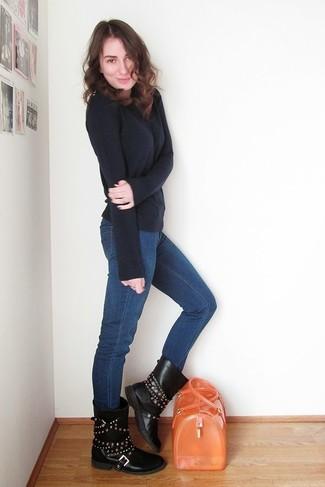 Comment porter: pull à col rond bleu marine, jean skinny bleu, bottes mi-mollet en cuir à clous noires, cartable en caoutchouc orange