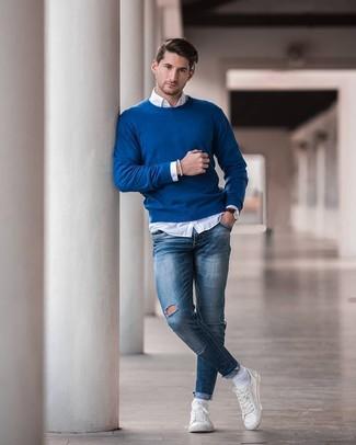 Comment porter: pull à col rond bleu, chemise à manches longues blanche, jean skinny déchiré bleu, baskets basses en cuir blanches