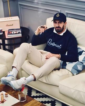 Comment porter: pull à col rond imprimé bleu marine, chemise à manches longues blanche, pantalon chino beige, chaussures de sport blanches
