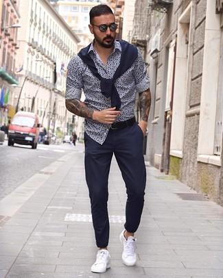 Comment porter: pull à col rond bleu marine, chemise à manches longues à fleurs bleu marine et blanc, pantalon chino bleu marine, baskets basses en cuir blanches
