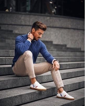 Comment porter un pantalon chino marron clair: Pense à marier un pull à col rond bleu avec un pantalon chino marron clair pour une tenue idéale le week-end. D'une humeur audacieuse? Complète ta tenue avec une paire de des baskets basses en toile imprimées blanches.