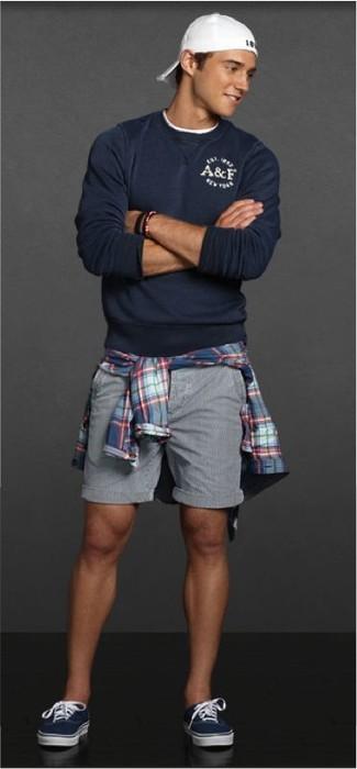Comment porter: pull à col rond bleu marine, chemise à manches longues écossaise bleue, short gris, baskets basses bleu marine