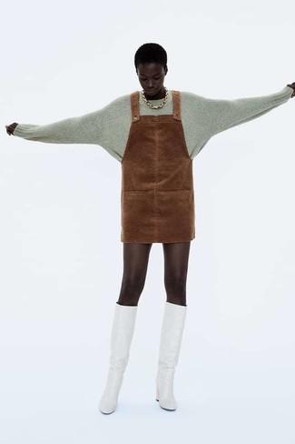 Comment porter: pull à col rond gris, robe chasuble en daim marron, bottes hauteur genou en cuir blanches, collier doré