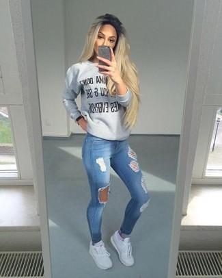 Comment porter: pull à col rond imprimé gris, jean skinny déchiré bleu, chaussures de sport blanches