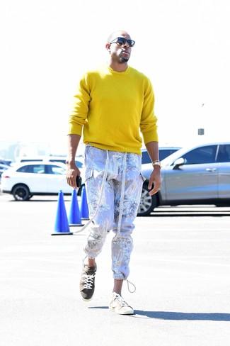 Comment porter: pull à col rond jaune, pantalon cargo imprimé violet clair, baskets basses en daim beiges, lunettes de soleil noires