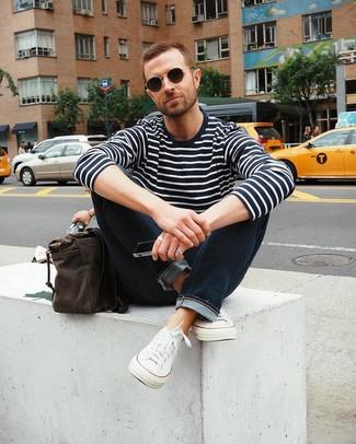 Comment porter: pull à col rond à rayures horizontales bleu marine et blanc, jean bleu marine, baskets basses en toile blanches, besace en cuir marron foncé