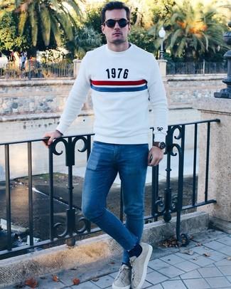 Comment porter: pull à col rond imprimé blanc, jean skinny bleu, baskets basses en cuir grises, lunettes de soleil bleu marine