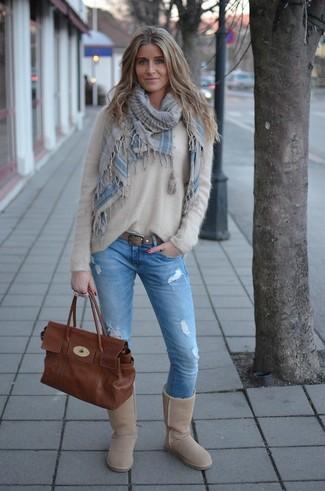 Comment porter: pull à col rond duveteux beige, jean skinny déchiré bleu clair, bottes ugg beiges, cartable en cuir marron