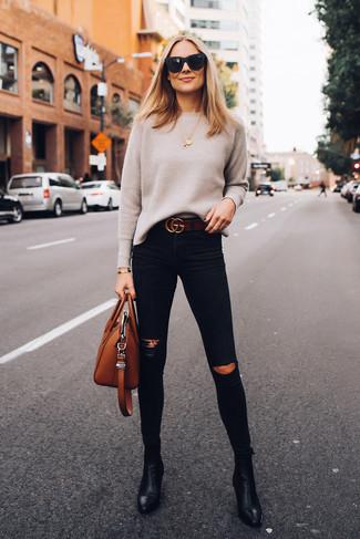 Comment porter: pull à col rond beige, jean skinny déchiré noir, bottines en cuir noires, sac fourre-tout en cuir tabac