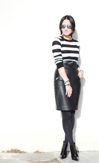 Comment porter: pull à col rond à rayures horizontales blanc et noir, jupe crayon en cuir noire, bottines en cuir noires, ceinture serre-taille en cuir noire