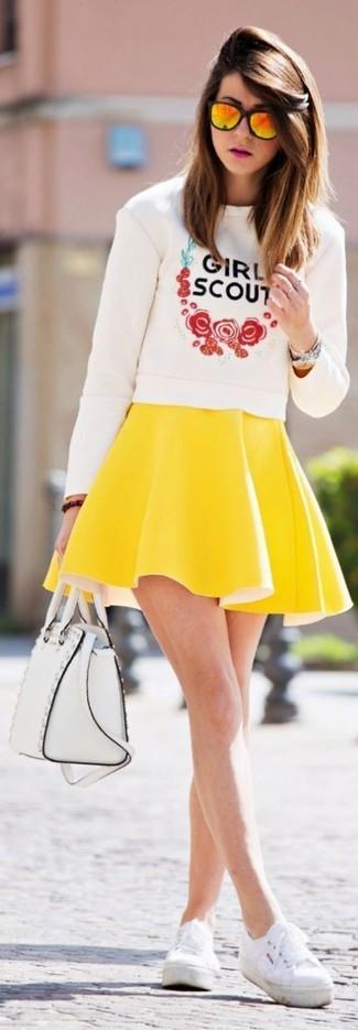 Comment porter: pull à col rond imprimé blanc, jupe patineuse jaune, tennis blancs, cartable en cuir blanc