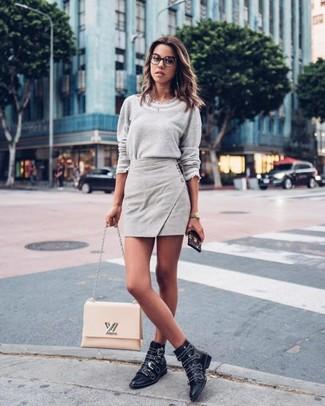 Comment porter: pull à col rond gris, minijupe grise, bottines en cuir à clous noires, cartable en cuir beige