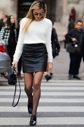 Comment porter: pull à col rond duveteux blanc, minijupe en cuir noire, chaussures richelieu en cuir noires, sac bandoulière en cuir noir