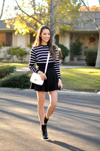 Comment porter: pull à col rond à rayures horizontales noir et blanc, jupe patineuse noire, bottines en cuir noires, sac bandoulière en cuir blanc