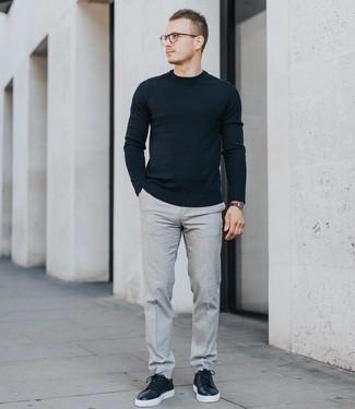 Comment porter: pull à col rond noir, pantalon de costume gris, baskets basses en cuir noires, montre en cuir marron foncé