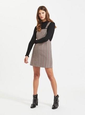 Comment porter: pull à col rond noir, robe chasuble écossaise grise, bottines en cuir noires
