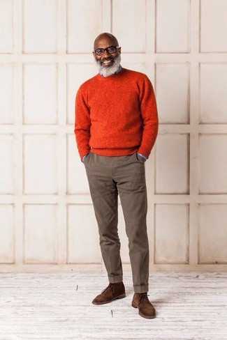 Comment porter: pull à col rond orange, chemise en jean bleu clair, pantalon chino marron, bottines chukka en daim marron
