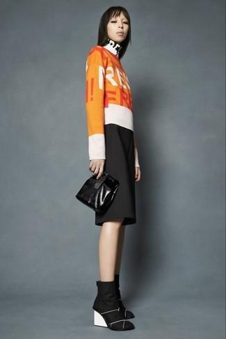 Comment porter: pull à col rond imprimé orange, jupe-culotte noire, bottines compensées en daim noires, pochette en cuir noire