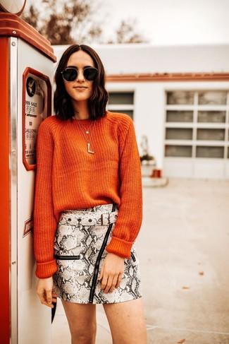 Comment porter: pull à col rond orange, minijupe en cuir imprimée serpent grise, lunettes de soleil noir et doré, pendentif doré