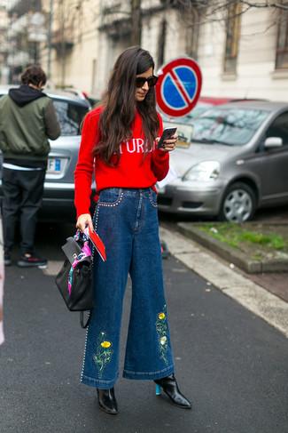 Comment porter: pull à col rond imprimé rouge, pantalon large en denim bleu, bottines en cuir noires, cartable en cuir noir