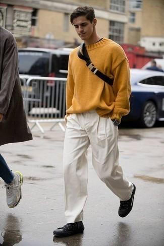 Comment porter un pull à col rond moutarde: Marie un pull à col rond moutarde avec un pantalon chino blanc pour affronter sans effort les défis que la journée te réserve. Une paire de des baskets basses en cuir noires apporte une touche de décontraction à l'ensemble.