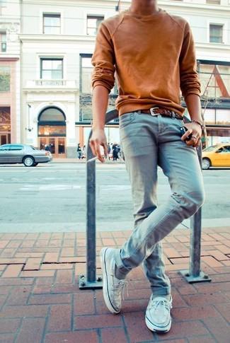 Comment porter: pull à col rond tabac, jean skinny bleu clair, chaussures bateau en cuir blanches, ceinture en cuir tressée marron