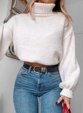 Comment porter: pull à col roulé en tricot blanc, jean skinny bleu, sac fourre-tout en cuir rouge, ceinture en cuir noire
