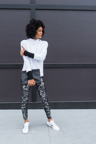 Comment porter: pull à col roulé en laine en tricot blanc, pantalon slim pailleté noir, baskets basses en cuir blanches et noires, pochette en cuir noire