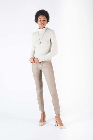 Comment porter: pull à col roulé en laine en tricot gris, jean skinny beige, escarpins en daim beiges, pendentif doré