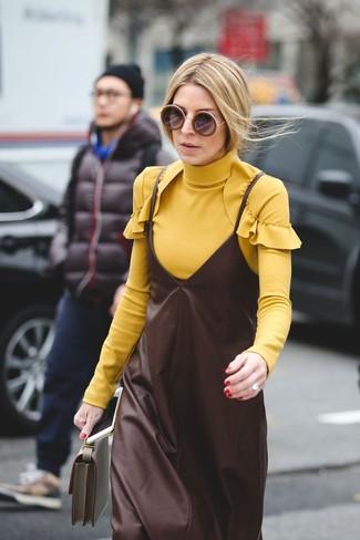 Associe un pull à col roulé jaune avec une pochette en cuir olive pour un ensemble de bureau stylé.