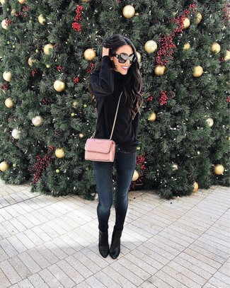 Comment porter: pull à col roulé en velours noir, jean skinny bleu marine, bottines en cuir noires, sac bandoulière en cuir matelassé rose