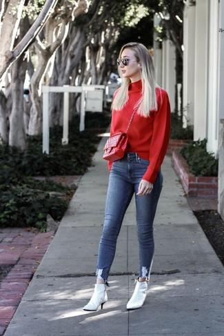 Comment porter: pull à col roulé rouge, jean skinny bleu, bottines en cuir blanches, cartable en cuir matelassé rouge