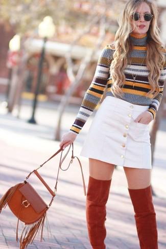 Comment porter: pull à col roulé à rayures horizontales multicolore, jupe boutonnée en denim blanche, cuissardes en daim rouges, sac bandoulière en daim à franges rouge