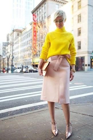 Comment porter: pull à col roulé en tricot jaune, jupe crayon rose, escarpins en cuir dorés, pochette en cuir dorée