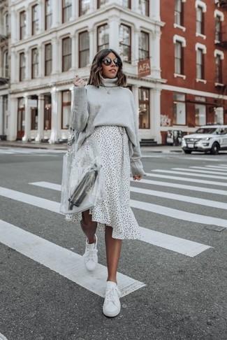 Comment porter: pull à col roulé en tricot gris, jupe mi-longue á pois blanche et noire, baskets basses en cuir blanches, sac fourre-tout en caoutchouc transparent