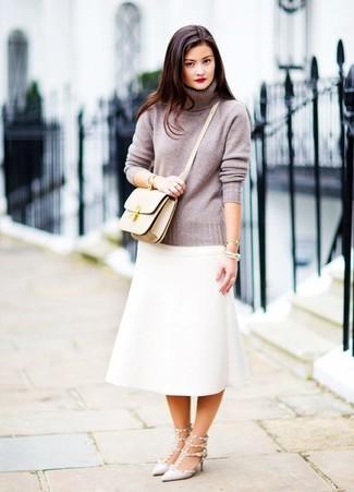 Tendances mode femmes: Pense à harmoniser un pull à col roulé gris avec une jupe mi-longue blanche pour aller au bureau. Assortis ce look avec une paire de des escarpins en cuir à clous gris.