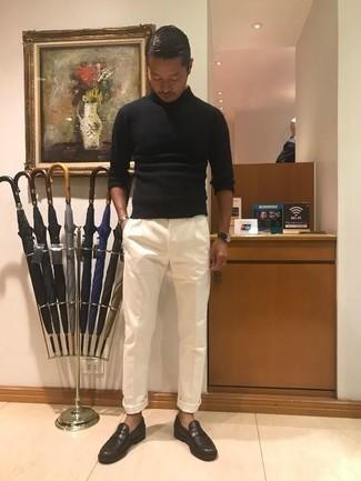 Comment porter un pantalon de costume blanc: Harmonise un pull à col roulé noir avec un pantalon de costume blanc pour un look classique et élégant. Termine ce look avec une paire de des slippers en cuir marron foncé.