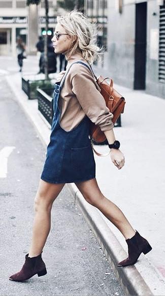 Comment porter: pull à col roulé beige, robe chasuble en denim bleu marine, bottines en daim marron foncé, sac à dos en cuir tabac