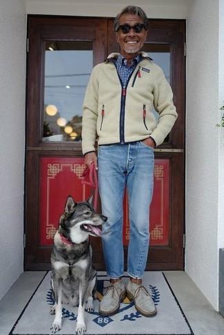 Comment porter: pull à fermeture éclair en polaire beige, chemise à manches longues à carreaux bleue, jean bleu clair, bottines chukka en daim grises