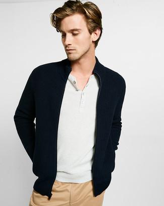 Comment porter: pull à fermeture éclair noir, t-shirt à col boutonné blanc, pantalon chino marron clair