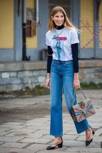 Comment porter: pull à fermeture éclair noir, t-shirt à col rond imprimé blanc, jean flare bleu, escarpins en cuir noirs