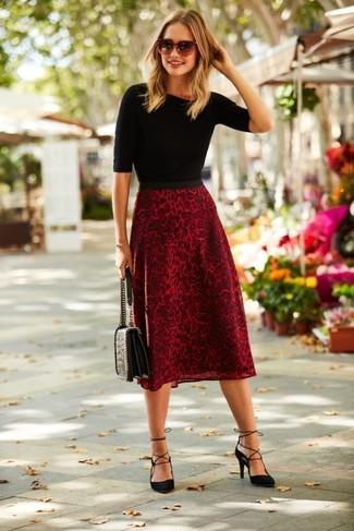 Comment porter: pull à manches courtes noir, jupe mi-longue imprimée léopard rouge, escarpins en daim noirs, cartable en cuir matelassé noir
