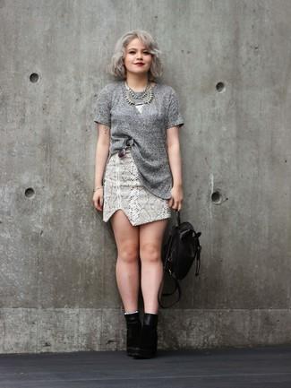 Comment porter: pull à manches courtes gris, minijupe en cuir imprimée serpent grise, bottines en daim noires, sac à dos en cuir noir