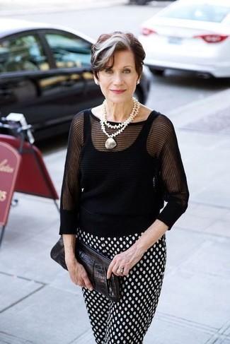 Comment s'habiller après 60 ans: Pense à porter un pull à manches courtes noir et un pantalon carotte á pois noir et blanc pour une tenue confortable aussi composée avec goût.