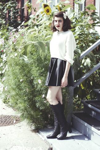 Comment porter: pull court en tricot blanc, jupe patineuse en cuir noire, bottes hauteur genou en cuir noires, nœud papillon blanc