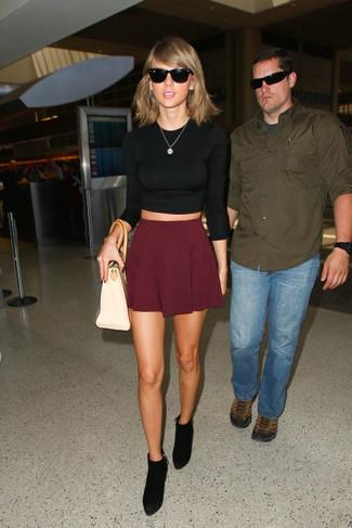 Tenue de Taylor Swift: Pull court noir, Jupe patineuse bordeaux, Bottines en daim noires, Sac fourre-tout en cuir beige