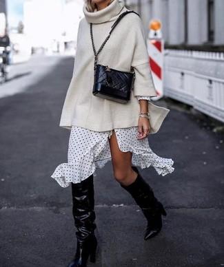 Comment porter: pull surdimensionné en tricot beige, robe drapée á pois blanche et noire, bottes hauteur genou en cuir noires, sac bandoulière en cuir matelassé noir