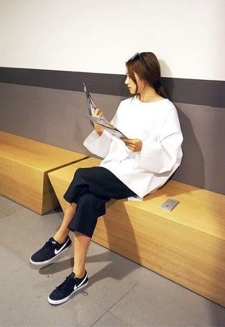 Comment porter: pull surdimensionné blanc, jupe-culotte noire, baskets basses noires